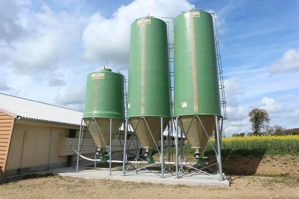 3 silos à grain coloris vert avec l'option goulotte d'ensachage
